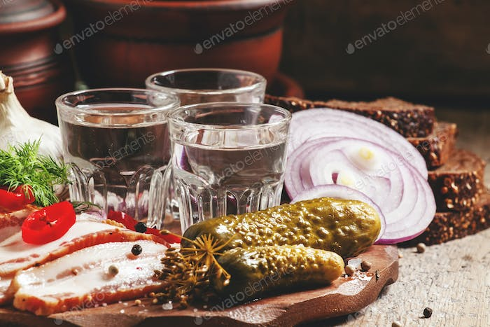 Russian tradition: cold vodka and a snack of bacon, pickles, red onion and black bread