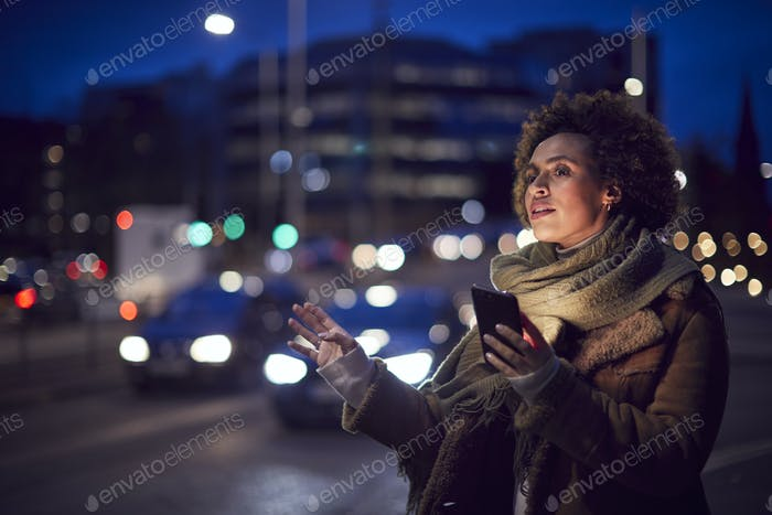 Woman On City Street At Night Ordering Taxi Using Mobile Phone App