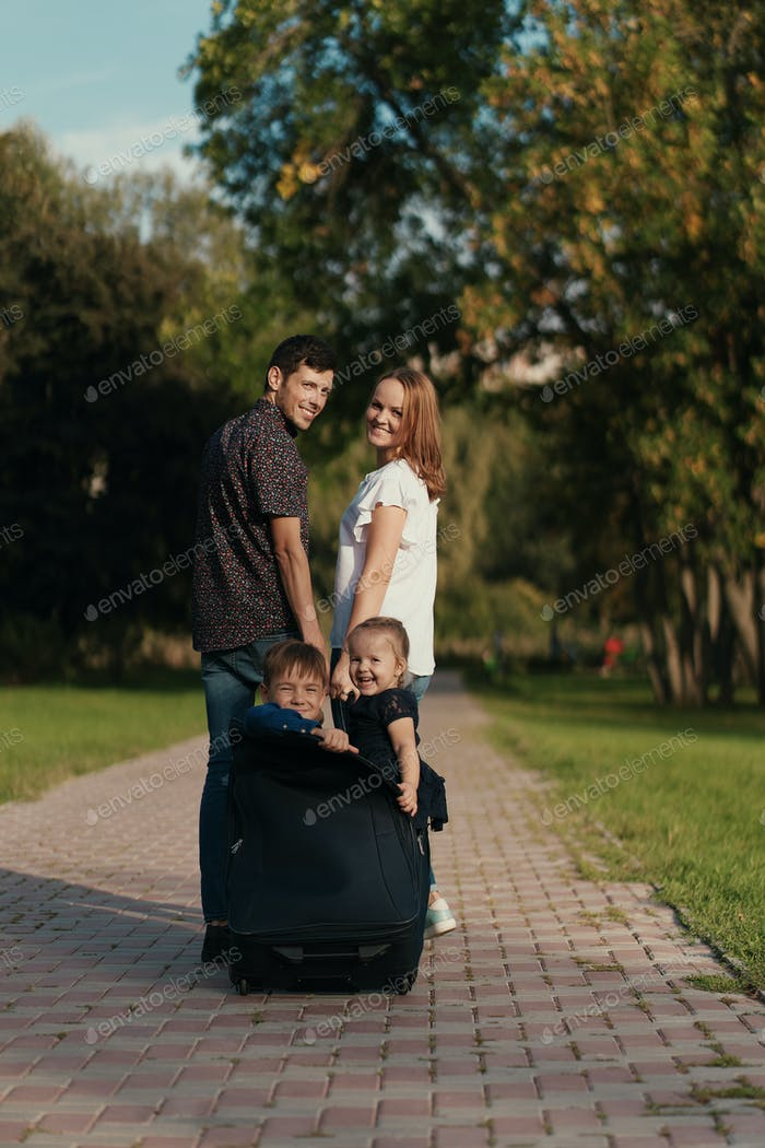 Happy couple carry their kids in a briefcase while playing