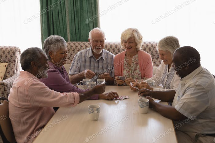 Front view of group of senior people playing cards in living room at home
