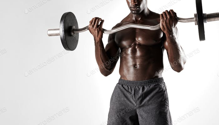 Young fit man lifting barbell on grey background