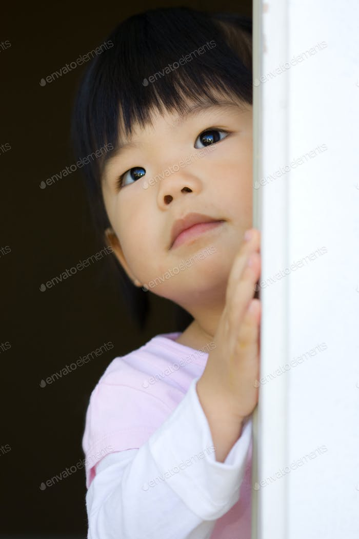 Pretty little child stands behind a door