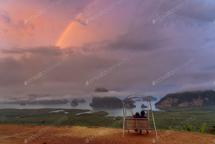 Scene of lovers sitting and pointing to the rainbow over the Fantastic Landscape