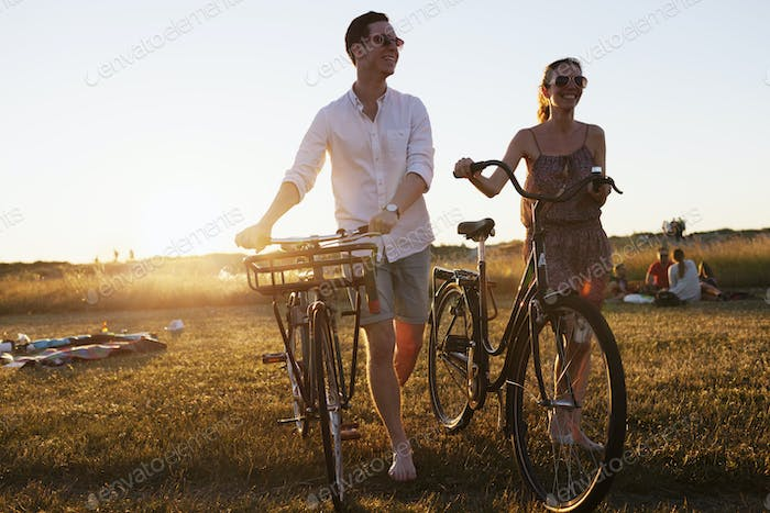 Happy friends walking with bicycle on field