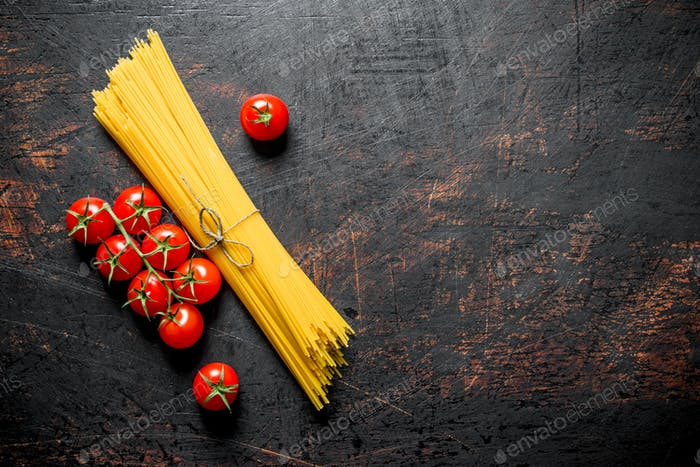 Raw spaghetti with tomatoes on a branch.