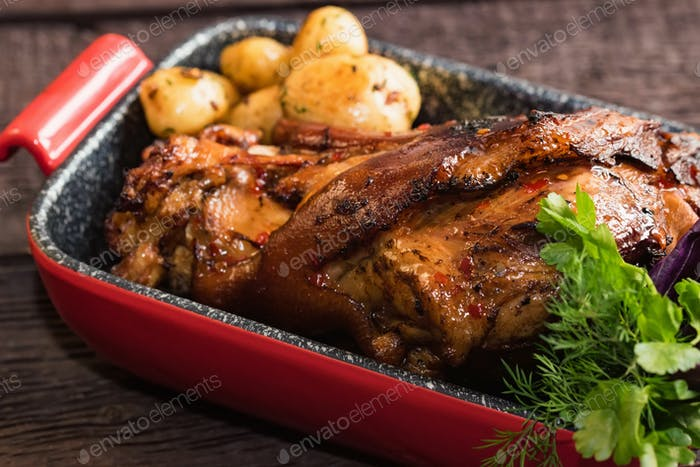 Close up roast pork knuckle served with boiled potatoes in tray
