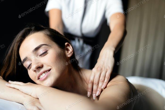 Junge schöne Frau in Spa-Umgebung während der Massage Behandlung