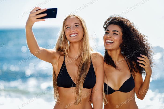 Two women taking selfie photograph with smartphone in the beach