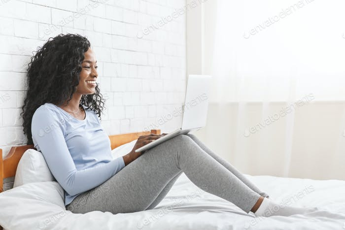 Pretty happy girl sitting on bed, using laptop