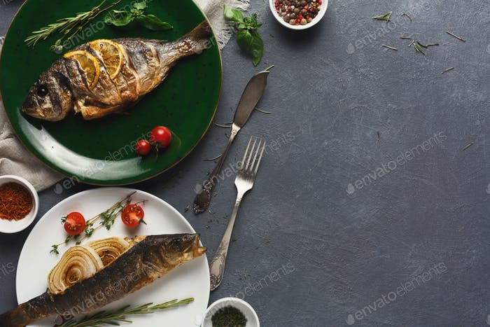 Whole grilled dorado and sea bass on table