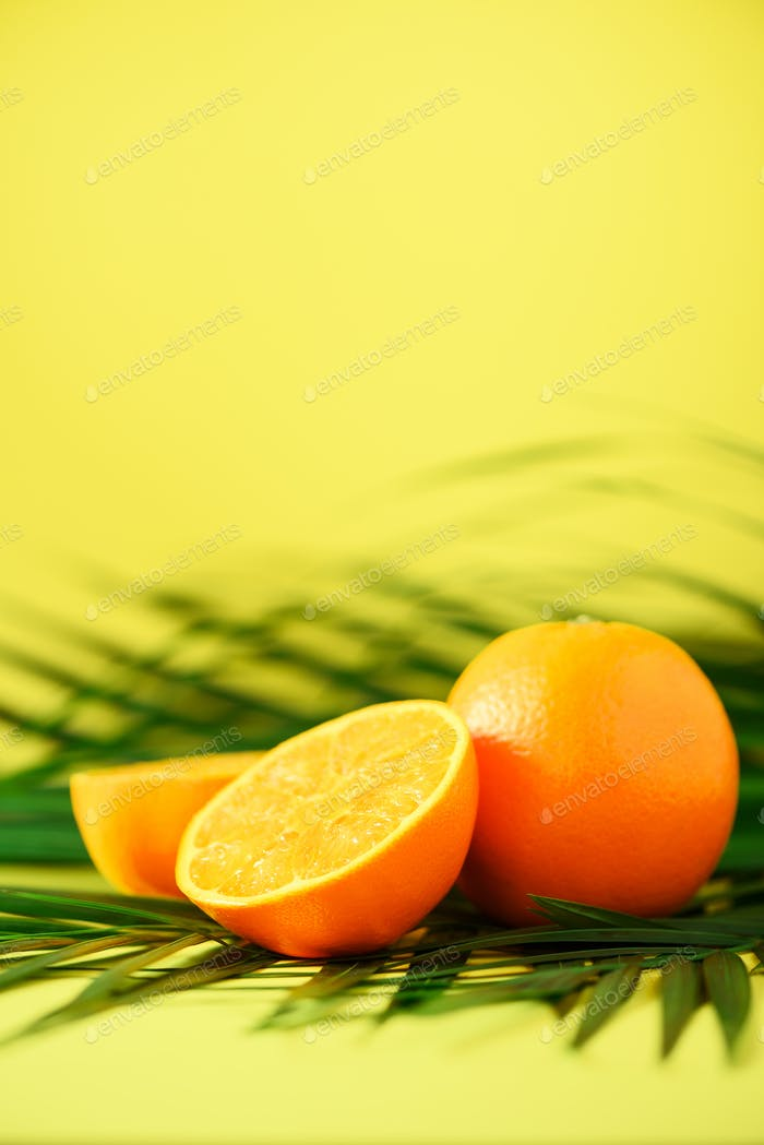 Orange fruit over tropical green palm leaves on yellow background. Copy space. Pop art design