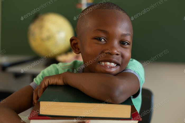 Schoolboy smiling at the camera while leaning on books at desk in a classroom at elementary school