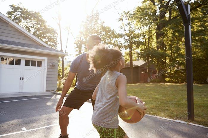 Vater und Sohn spielen Basketball auf Auffahrt zu Hause