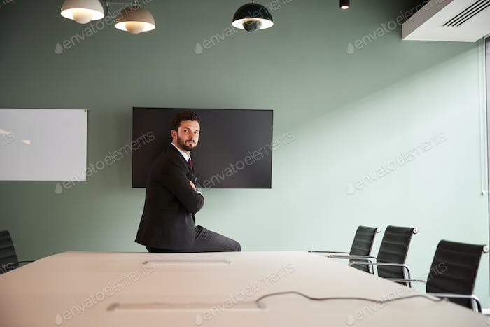 Portrait Of Young Businessman Sitting On Boardroom Table At Graduate Recruitment Day