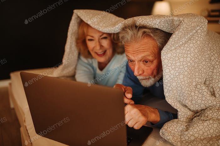 Photo of senior couple browsing internet on laptop while lying in bed covered with blanket.