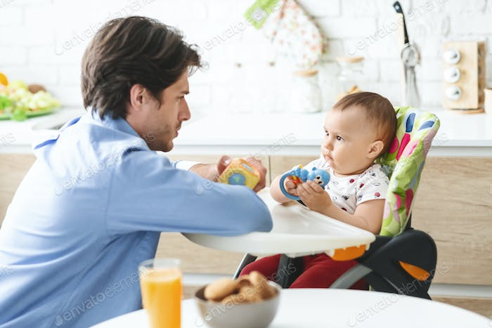 Curious baby in high chair playing with daddy at kitchen