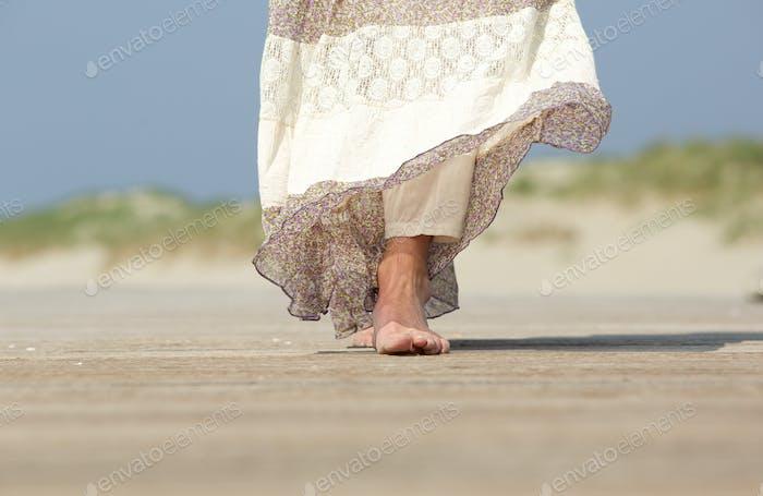 Female feet walking forward at the beach