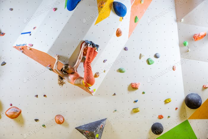 Young woman bouldering challenging route in climbing gym