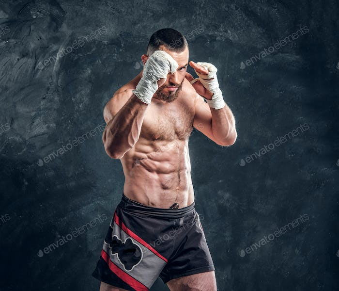 Portrait of muscular fighter with nacked torso