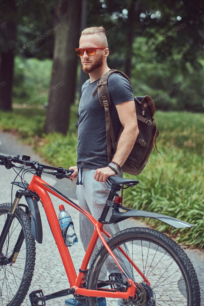 Handsome redhead male standing with a bicycle and backpack outdoors