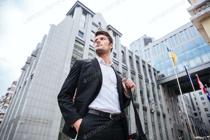 Businessman standing outdoors near business center