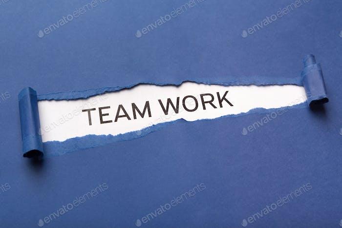 Text Teamarbeit auf weißem Hintergrund hinter zerrissenem blauem Papier