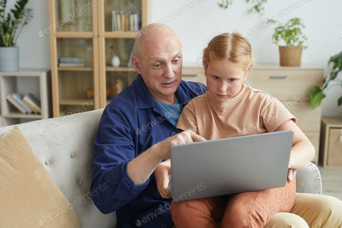Senior Man Using Laptop with Granddaughter