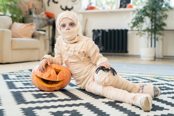 Little boy mummy with spider and jack-o-lantern lying on the floor