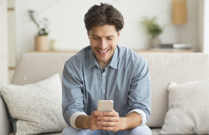 Happy Guy Browsing On Smatphone Sitting On Couch At Home