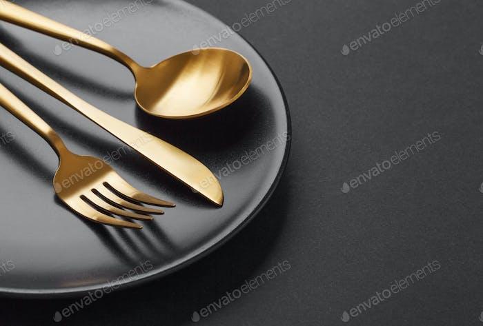 Gold cutlery set on black background