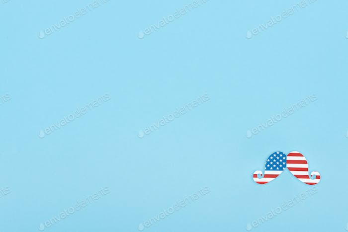 Top View of Mustache Made of American Flag on Blue Background With Copy Space