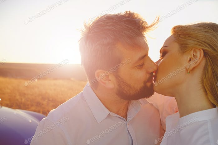 Couple kissing on the background of a sunset