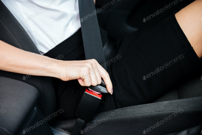 Woman sitting in car and putting on her seat belt
