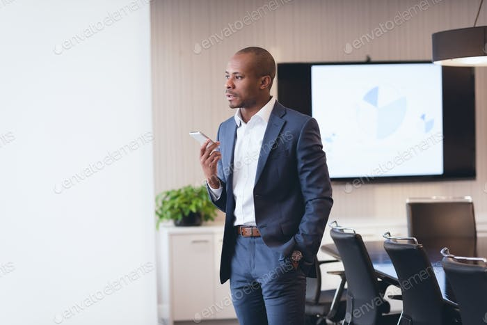 Young mixed race businessman speaking at mobile phone and looking away standing in boardroom