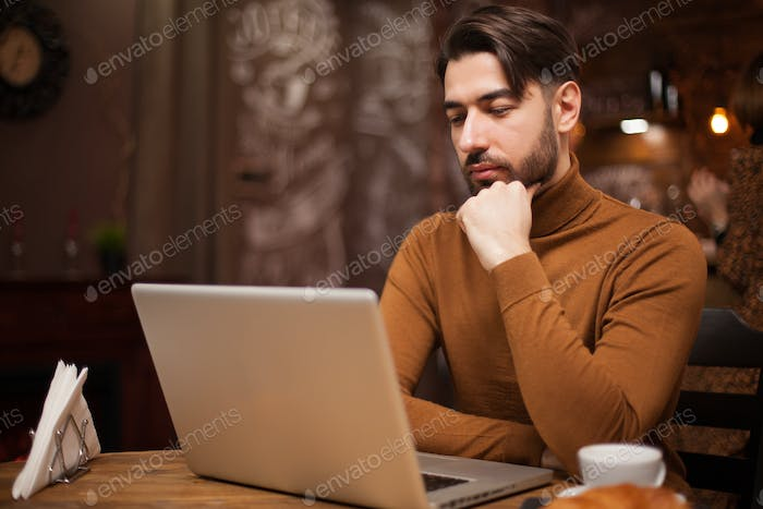 Bearded businessman working on his laptop in a vintage coffee shop