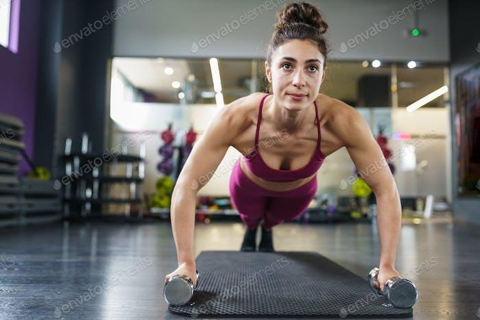 Mujer haciendo ejercicios de flexiones con mancuerna en un entrenamiento de fitness