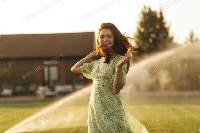 Trendy girl with foxy hairstyle, bandage on neck and cool hat in beautiful summer dress looking int