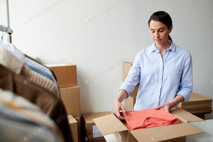 Young casual employee putting folded casualwear into box in process of packing