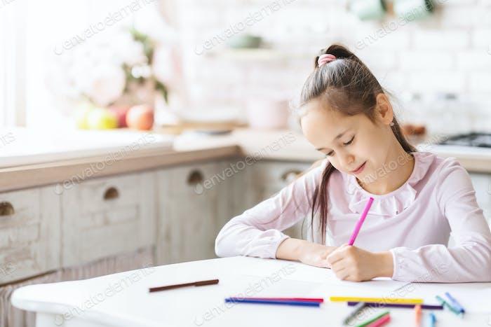 Niedlich kleines Mädchen sitzen in Küche und Zeichnung