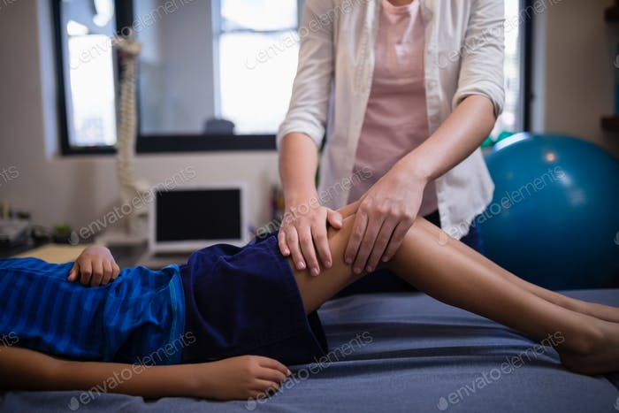 Midsection of female therapist massaging calf with boy