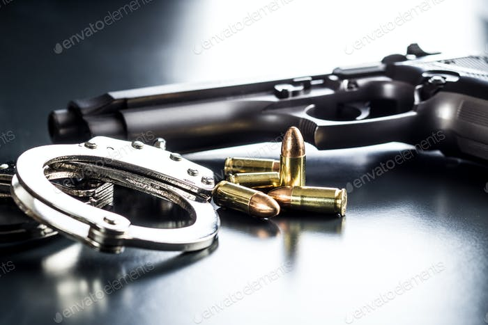 Pistol bullets, handgun and handcuffs.