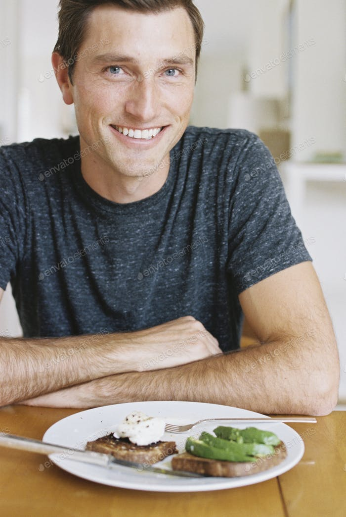Man sitting in front of a plate of food at a table, looking at camera, smiling.