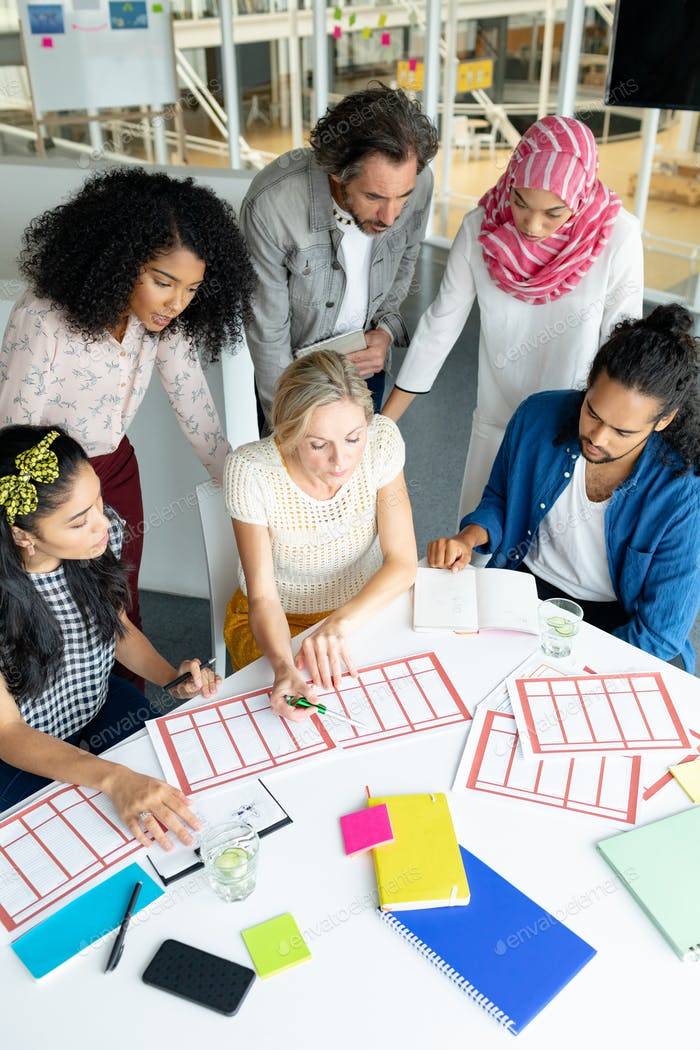 Diverse business people discussing together over documents at conference room