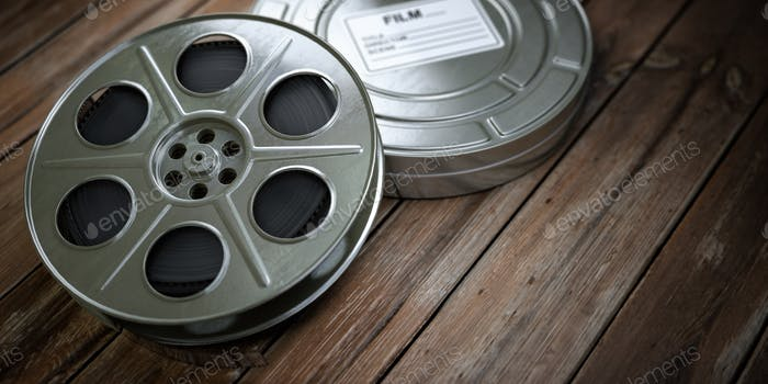 Vintage film reel with filmstrip on wood background. Video, cine