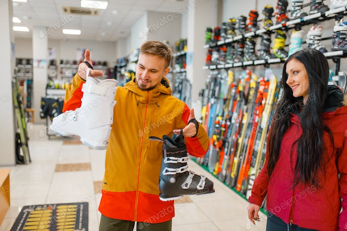 Couple choosing ski boots, shopping, sports shop