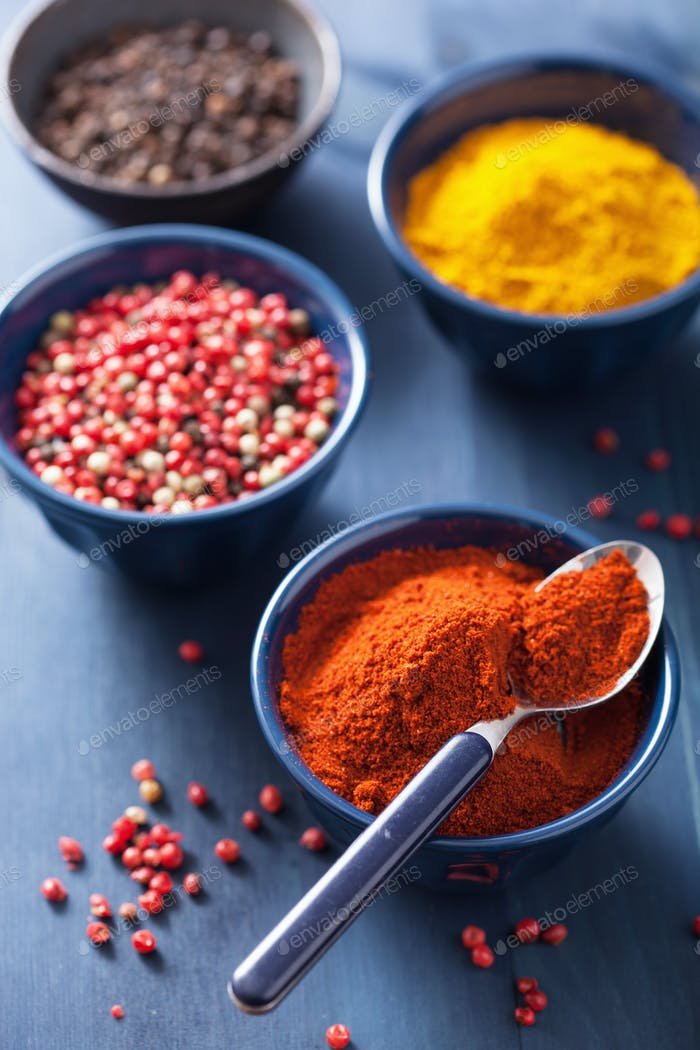 spices in bowls: curry, pink black pepper, paprika powder