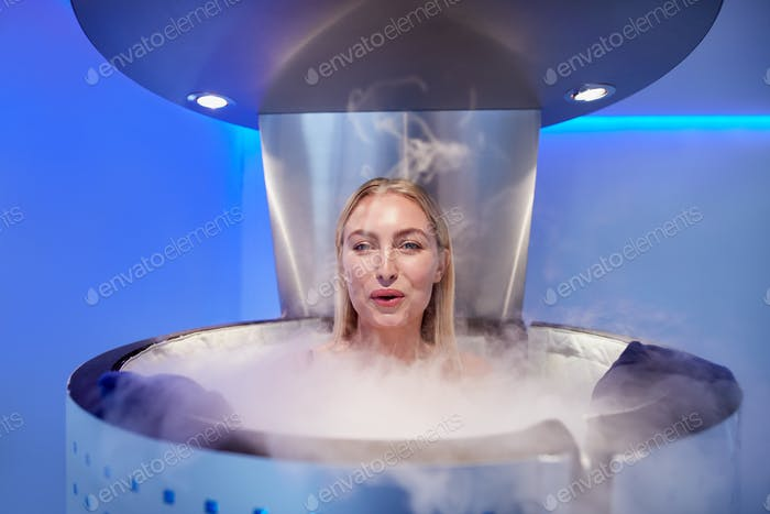 Woman in a whole body cryotherapy cabin