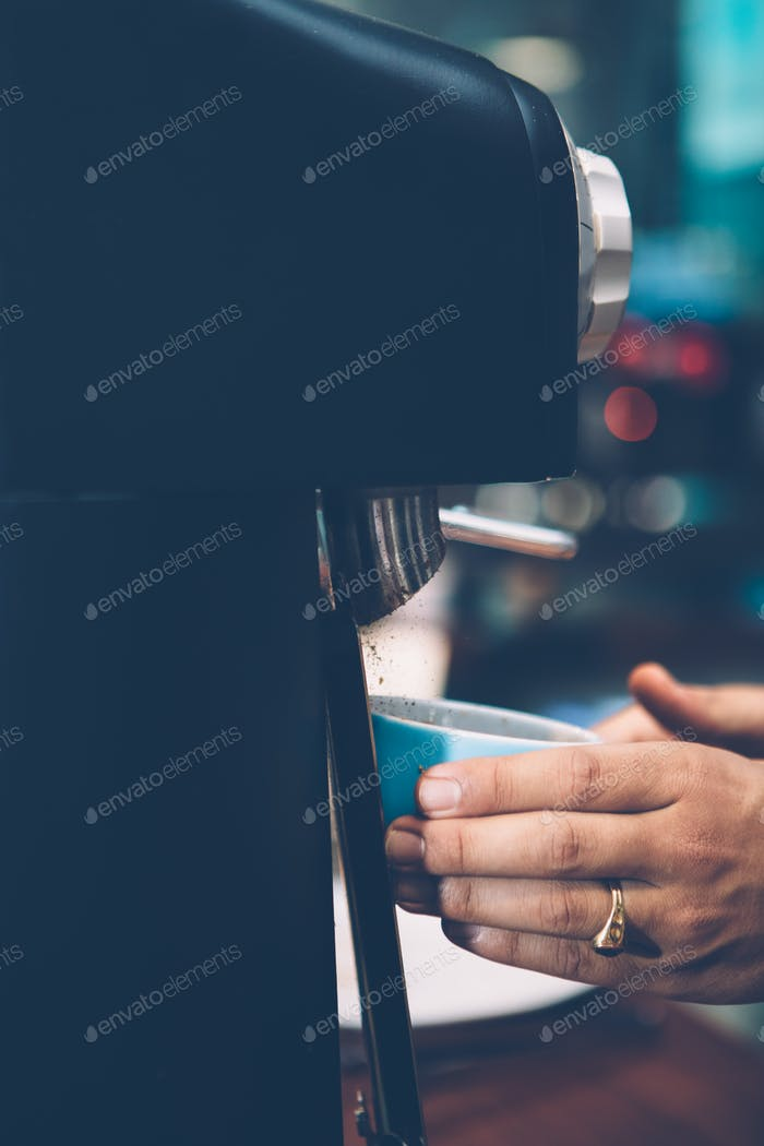 Hands pouring cup with ground coffee