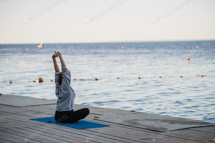 Morning shot of a girl in lotus position doing stretching yoga exercises on the pier