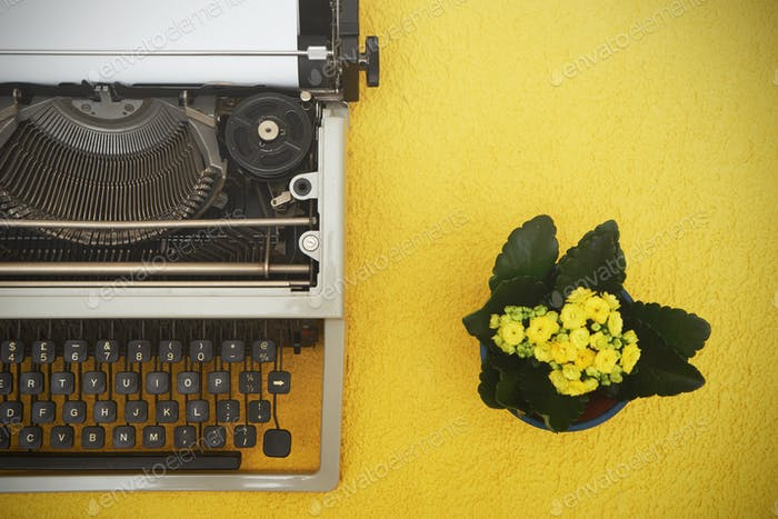 Vintage typewriter on  yellow background